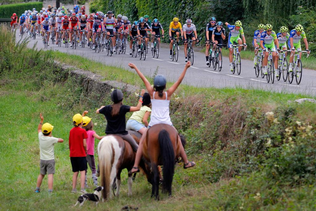 Young fans on horse back cheer on the peleton during stage 17.