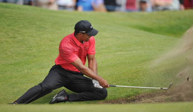 ON BENDED KNEE: Tiger Woods plays from his knees as he attempts to hit out of a bunker on the sixth hole.