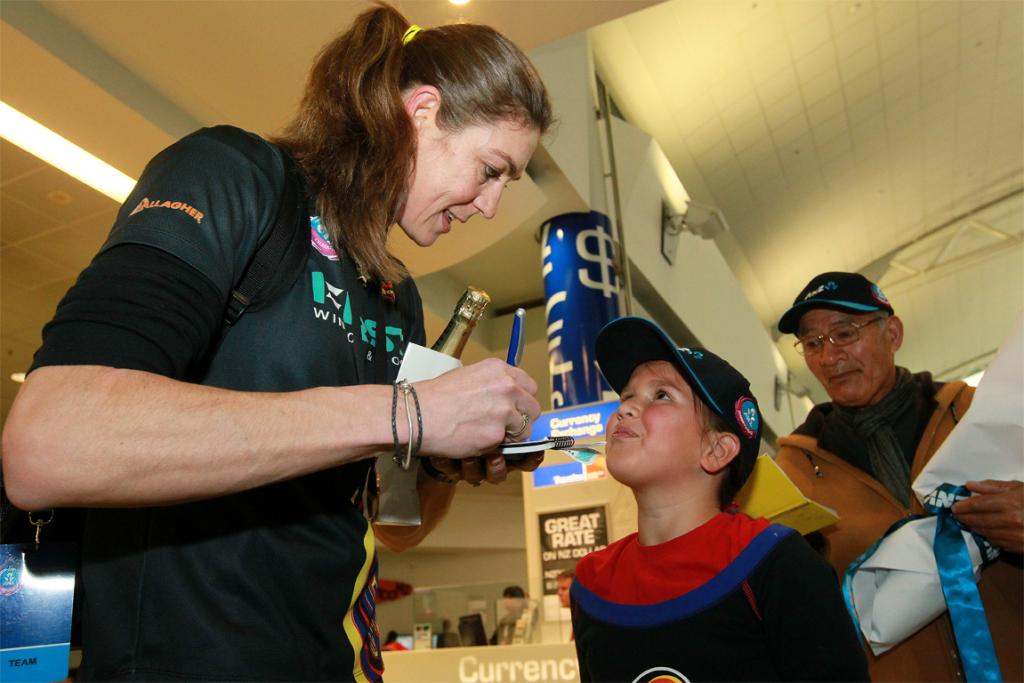 Irene van Dyk signs an autograph for fan Natalia Coppins on the Magic's arrival at Auckland Airport.