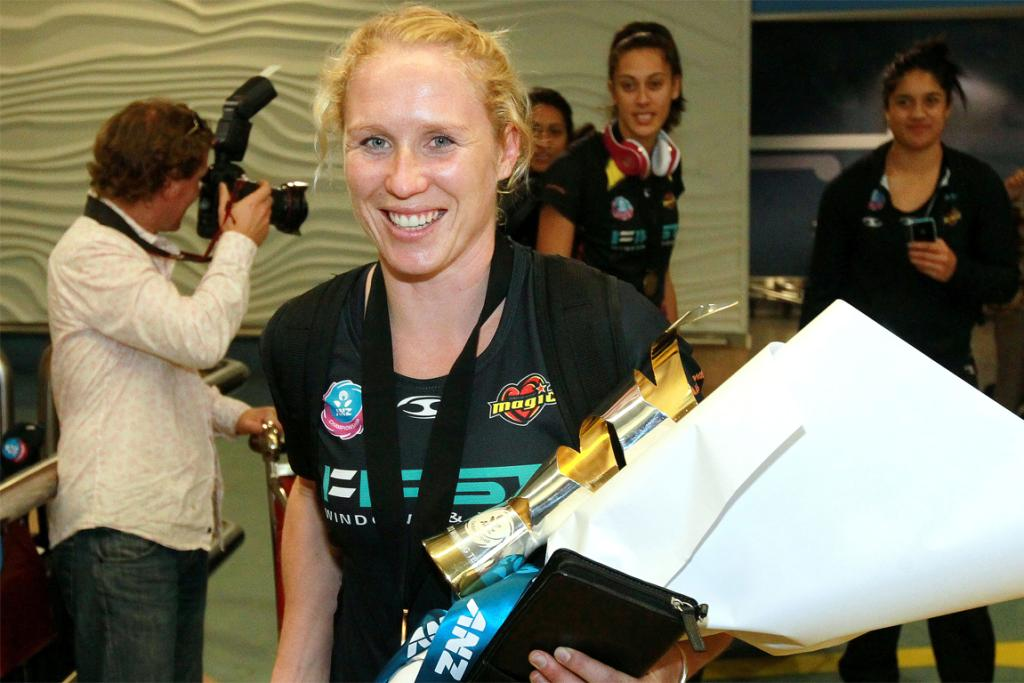 Captain Laura Langman clings to the trophy as the triumphant Magic arrive at Auckland Airport.
