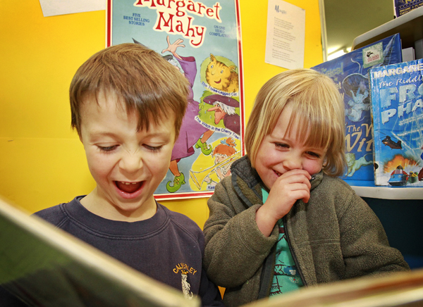 Still enthralling: Daniel Coates, 6, and sister Eleanor Coates, 4, read a Margaret Mahy book from a display set up in the Blenheim Library to celebrate the author's work. Mahy died on Monday