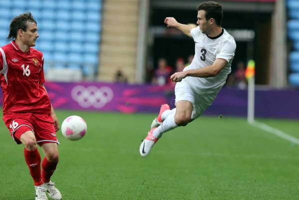 New Zealand's Ian Hogg is airborne trying to keep the ball in play during his team's loss to Belarus at the London Olympics.