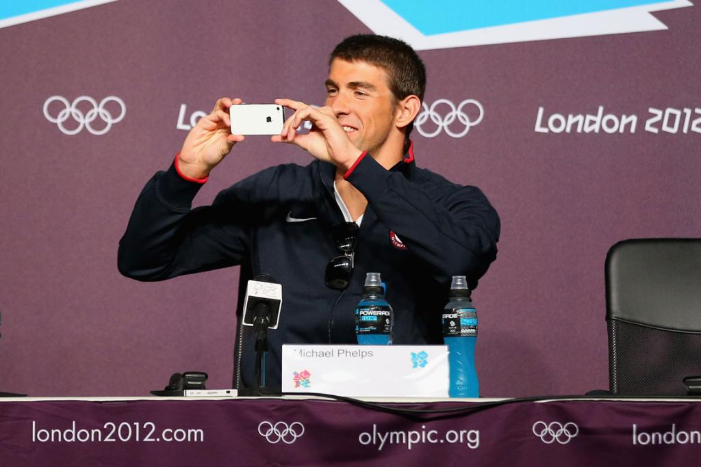 Michael Phelps takes a photo during a press conference at the London Olympics.
