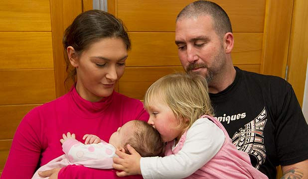 HAPPY TIMES: Alyssa Barker, with parents Sam and Scott, kisses her baby sister Kashine during the press conference at Henderson Police station earlier today.
