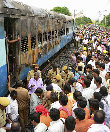 GUTTED BY FIRE: Onlookers stand next to a burnt carriage of a passenger train parked at the Nellore railway station.