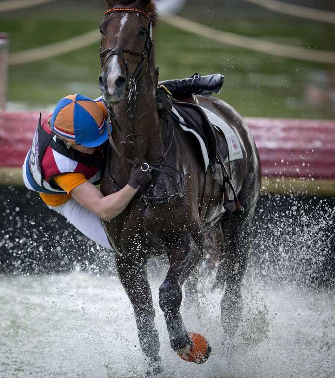 Elaine Pen from the Netherlands, riding Vira, strikes trouble through the water jump during the cross country phase of the equestrian at Greenwich Park during the 2012 London Olympic Games.
