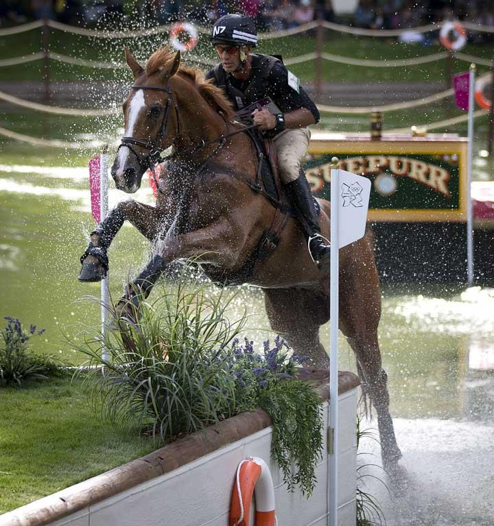 New Zealander Andrew Nicholson, riding Nereo, comes through the water jump during the cross country phase of the equestrian at Greenwich Park during the 2012 London Olympic Games.