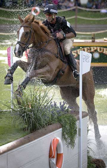 New Zealander Andrew Nicholson, riding Nereo, comes through a water jump during the cross country phase of the equestrian at Greenwich Park during the 2012 London Olympic Games.
