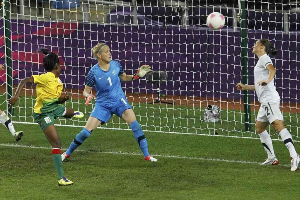 Cameroon's Gabrielle Onguene heads the ball to score against New Zealand during their women's football match at the City of Coventry Stadium during the London Olympics.