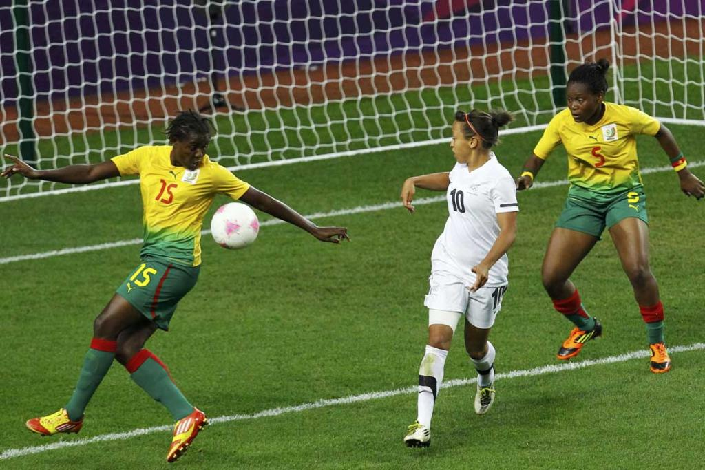 New Zealand's Sarah Gregorius (centre) watches as Cameroon's Ysis Sonkeng (left) scores an own goal against New Zealand during their women's football match at the City of Coventry Stadium during the London Olympics.
