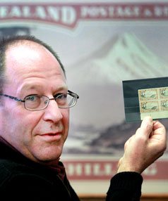 New Plymouth stamp dealer John Kilpatrick holds four 1935 stamps.