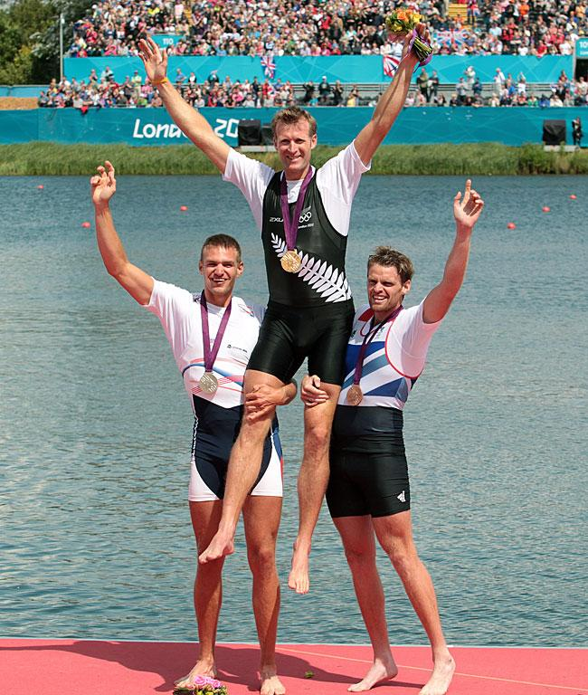 Andrej Synek (Cze) and Alan Campbell (GBR) hold up New Zealand's gold medal winner Mahe Drysdale after the medal ceremony.