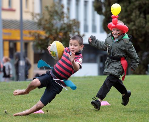 Jason Gage-Brown, 7,  and Cody Baker, 8, play touch in the Garden Place fan zone before the Super Rugby final.