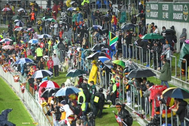 Fans take out their umbrellas as rain pours down before the Super Rugby final at Waikato Stadium