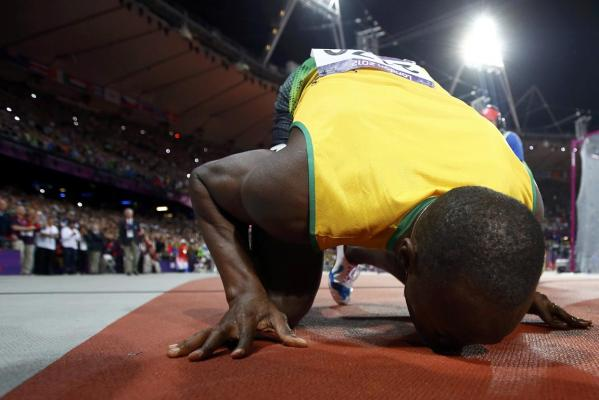 Jamaica's Usain Bolt kisses the track after winning the men's 100m final during the London 2012 Olympic Games.