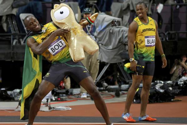 Jamaica's Yohan Blake (right) watches as his compatriot Usain Bolt holds up a ''Wenlock'', one of the London 2012 Olympics mascots, as he celebrates winning the men's 100m final.