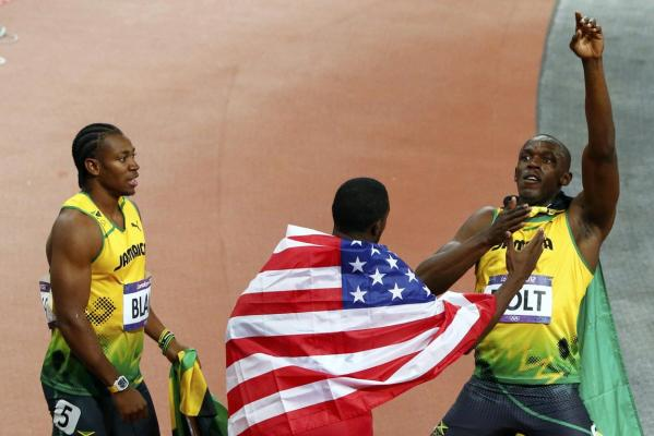 Jamaica's Usain Bolt celebrates after winning the London Olympics' men's 100m final next to his compatriot, second place finisher Yohan Blake (left), and third place finisher Justin Gatlin of the US.