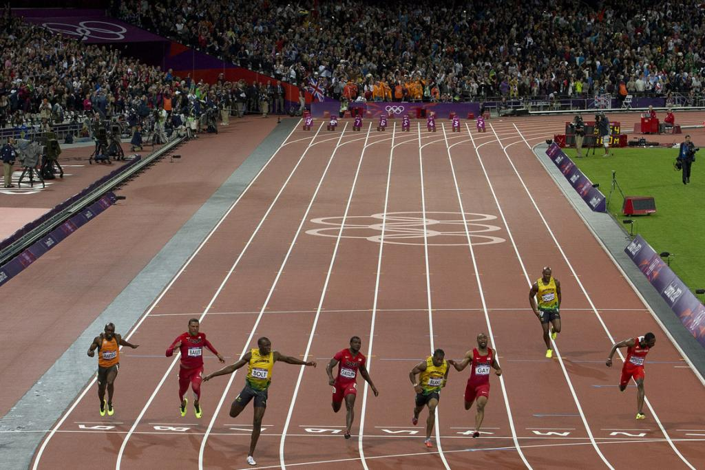 Usain Bolt crosses the line to win the 100m final ahead of fellow Jamaican Johan Blake.