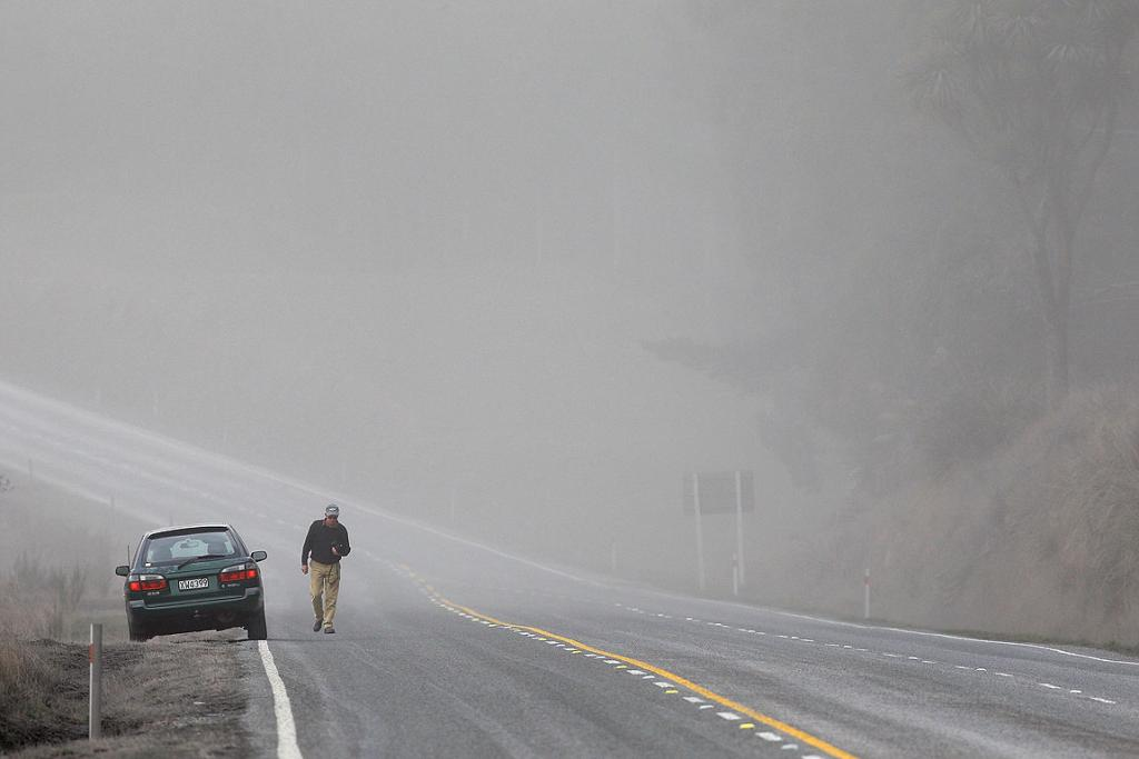 A motorist is surrounded by a cloud of ash on SH1 after Mt Tongariro erupted for the first time in over 100 years.