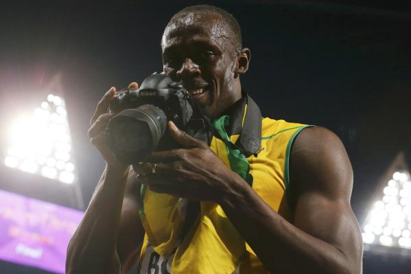 Jamaica's Usain Bolt takes pictures with a photographer Jimmy Wixtrom's camera as he celebrates after winning the men's 200m final at the London 2012 Olympic Games.