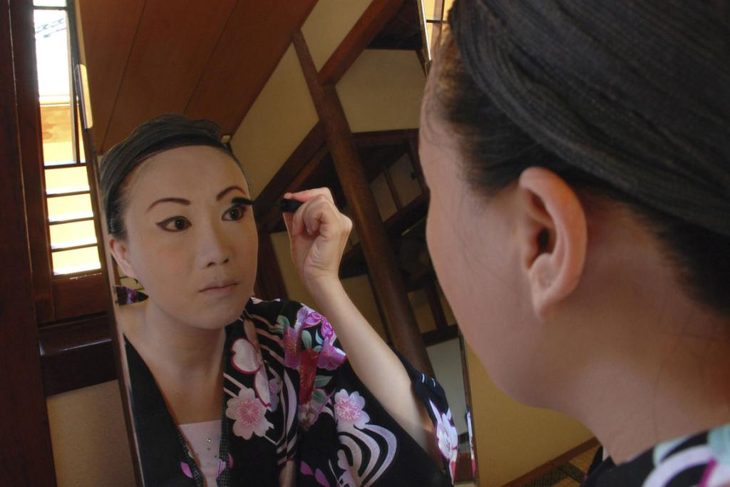 Chinese geisha trainee Rinka, born as Zhang Xue, puts on makeup at a geisha school in the port town of Shimoda.