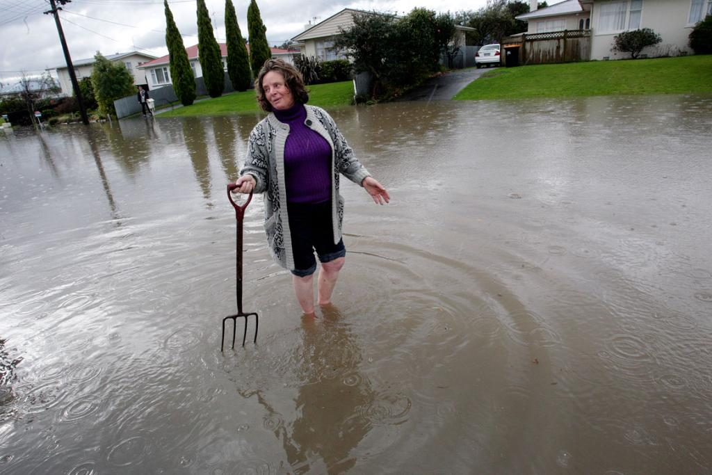 WATER-LOGGED STREET: A Nairn Crescent resident searches for the blocked culvert.