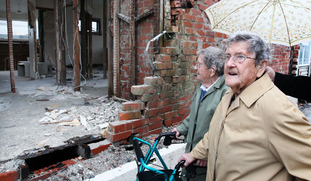 LIFE CHANGES: Christchurch twins Helen and Edna Yates look at the house they lived in for 95 years before it is demolished because of earthquake damage.