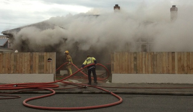 Firefighters outside a Grace St house that caught on fire late this afternoon in Invercargill.