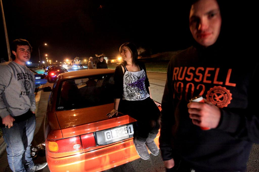 ON THE TURPS: Young people, most of them drinking, hang around their cars, hoping the police will leave them alone.