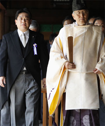 STRAINED RELATIONS: Minister Yuichiro Hata (L) and other lawmakers are led by a Shinto priest after offering prayers to war dead at Yasukuni Shrine in Tokyo