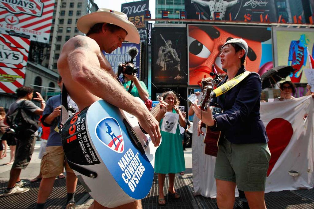 Times Square entertainer Naked Cowboy plays guitar with a protester demonstrating in solidarity with the Russian punk band Pussy Riot.