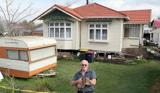Phil Thompson, with his cat Boss, by the caravan that has been home for 18 months, adjacent to his uninsured house.