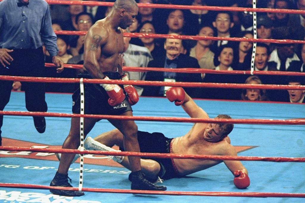 Mike Tyson looks down at a knocked out Francois Botha.
