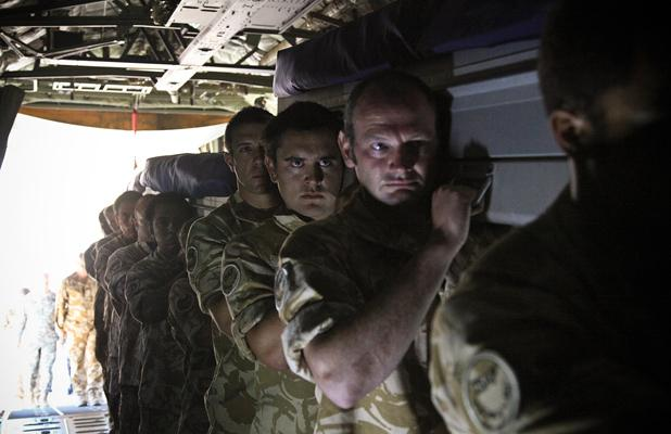 TRADITION: A bearer party carry their comrades onto the aircraft for the return journey home.