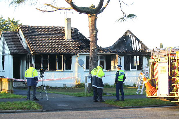Firefighters and police survey the scene of the large house fire on Holland Rd on Wednesday morning.
