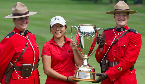 REWRITING HISTORY BOOKS: Lydia Ko poses with the trophy with two members of the Royal Canadian Mounted Police.