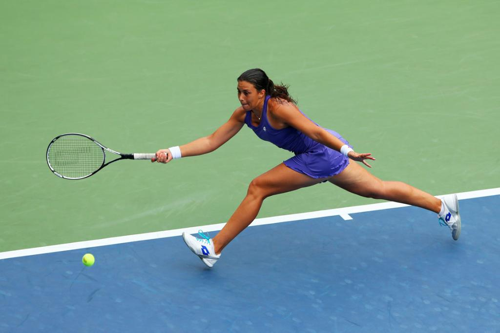 Marion Bartoli of France stretches to reach a ball in her opening round match.