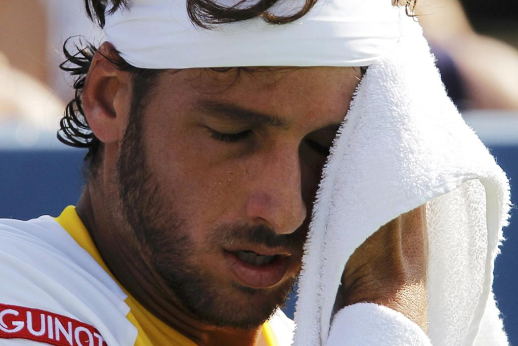Feliciano Lopez wipes the sweat from his face during his four set loss to Andy Murray.