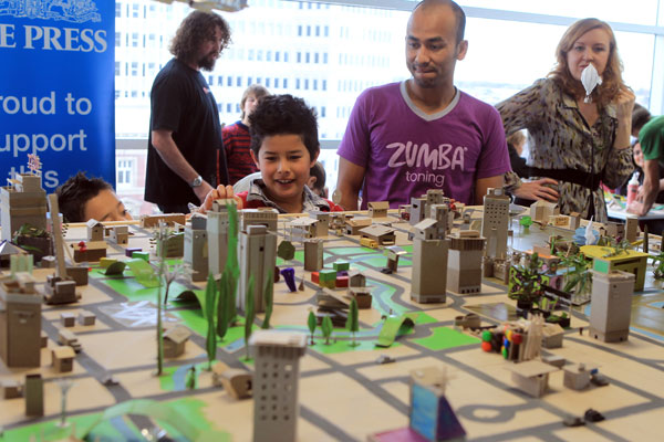 3D Cardboard City being constructed by the public run by Californian artist, Kiel Johnson, on the 7th floor of Press House. Alok Pradhan with sons, Rico, 6, left, and Marli, 8, check out the progress so far after adding a building of their own.