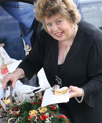 Margaret McHugh serves customers at the Christmas Farmers Market