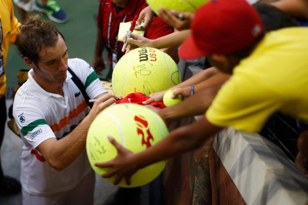Frenchman Richard Gasquet signs autographs after defeating American Steve Johnson.