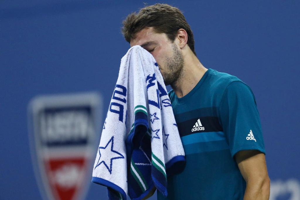 Gilles Simon wipes sweat from his face during his defeat against American Mardy Fish.