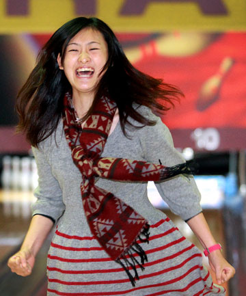 STUNNING STRIKE: Haruka Taniguchi, 19, who is in Taranaki with nine other Nihon University students, celebrates bowling the first strike during a visit to New Plymouth's Bowlarama yesterday.