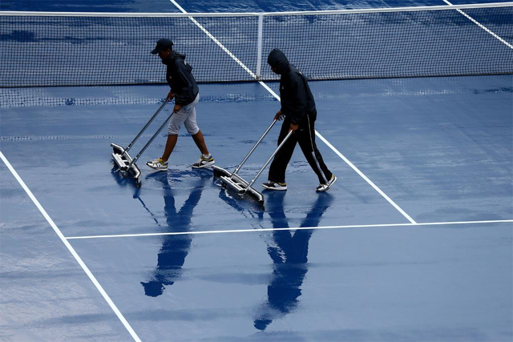 Grounds crew dry the court after rain suspended play.