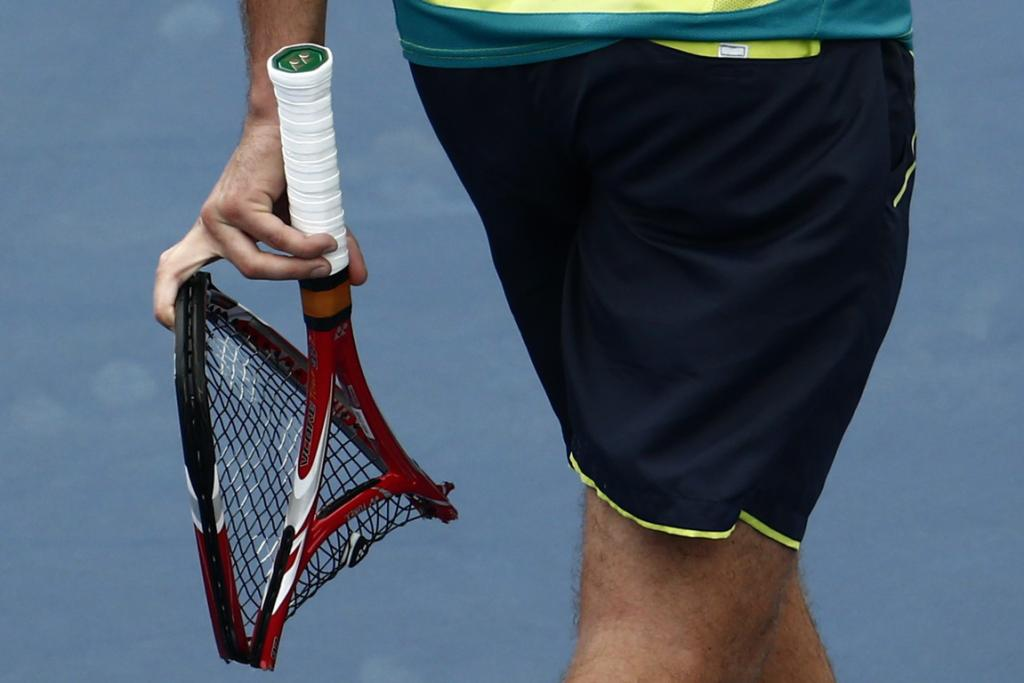 Stan Wawrinka smashes his racket in frustration during his loss to Novak Djokovic.