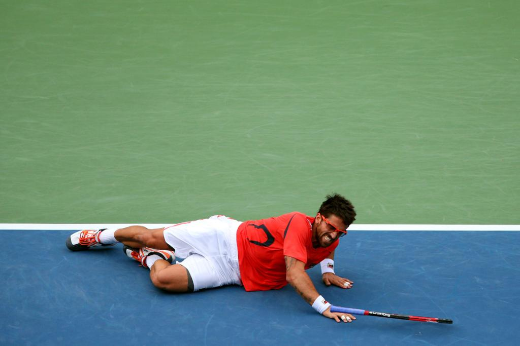 Janko Tipsarevic takes a tumble during his quarter-final against David Ferrer.