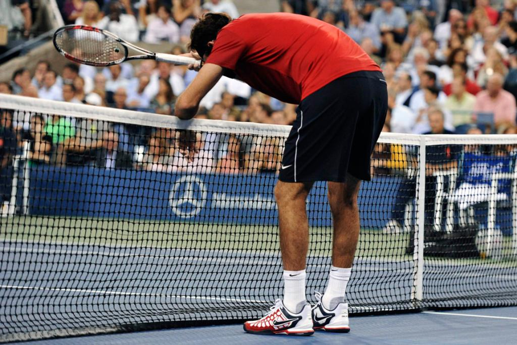 Juan Martin del Potro leans against the net after losing a point against Novak Djokovic.