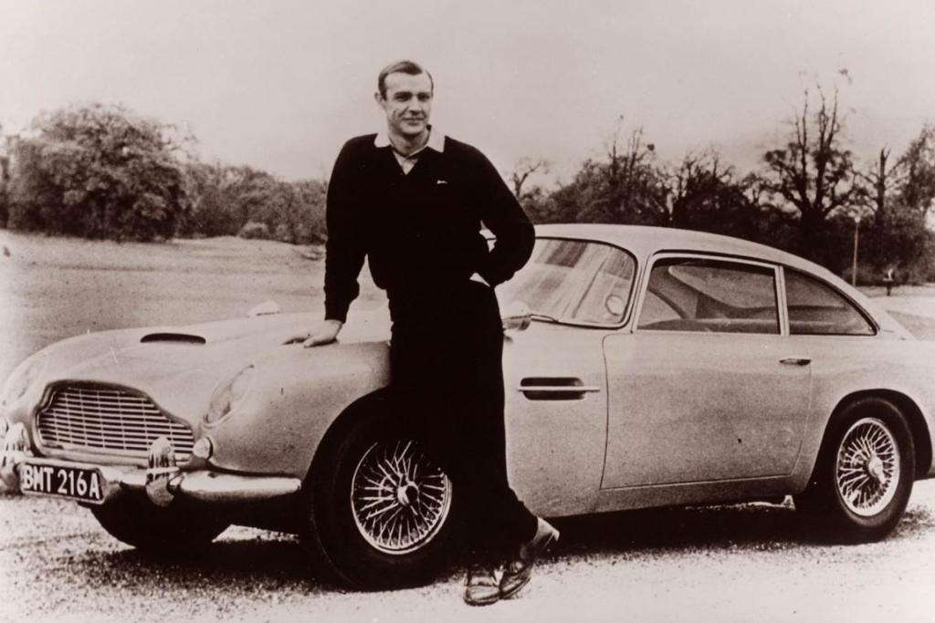 James Bond (Sean Connery) leans on the Aston Martin DB5 from the movie Goldfinger.