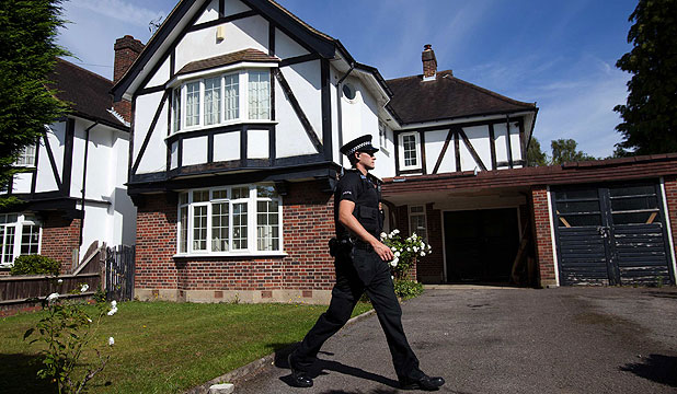 SEARCH FOR MOTIVE: A police officer at the home of Saad al-Hilli in Claygate, south of London.