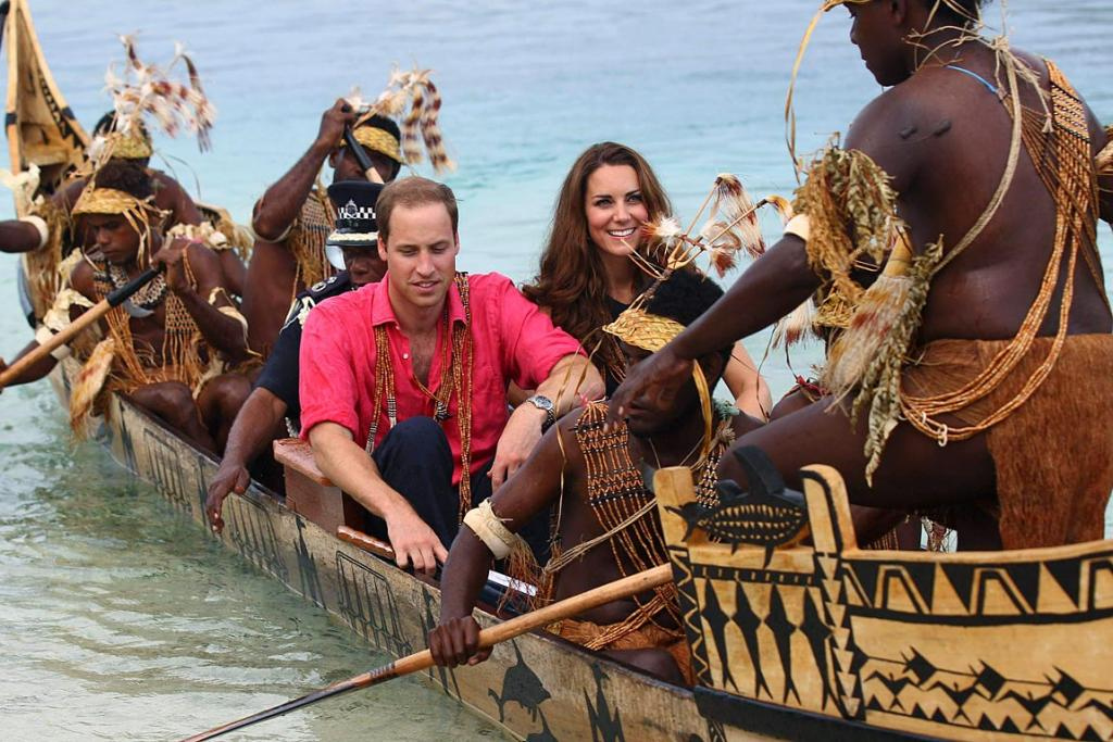 Kate and William ride a traditional war canoe as they arrive in Tavanipupu, Solomon Islands.